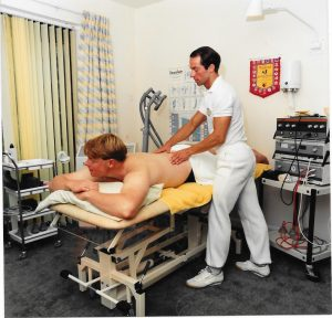 Physiotherapist Greg Welch based in Bournemouth manipulating a man on a physiotherapists table face down