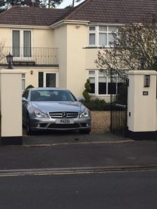 Picture of a large house with pillars and a gate to the front in which sits a car with the letters p h z i and o on the number plate
