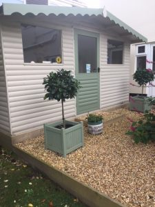 Picture of a stand alone building with a light green door and arches with windows to either side of the door and gravel frontage with smart bushes in pots