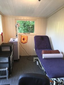 Picture of a physiotherapists table and various pieces of medical equipment with a window in the background