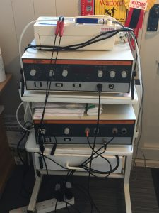 Picture of waist height trolley on wheels with several shelves containing electrical medical equipment