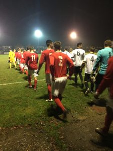 Picture of two teams of footballers one in white shirts the other in red and white heading out onto the pitch in two straight lines