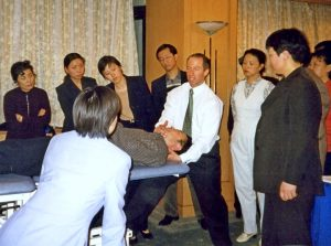 Picture of a group of students watching physiotherapist with hands on the head of a man lying on a physiotherapy couch