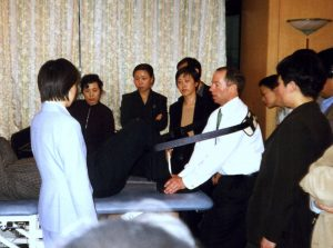 Picture of a group of students watching physiotherapist with hands on the feet of a man lying on a physiotherapy couch
